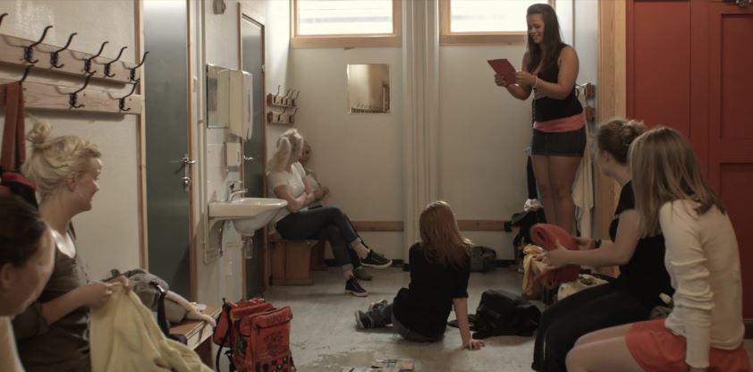 Ei jente står på ein benk i jentegarderoben og les frå ei bok. Dei andre jentene ser på henne. Foto.