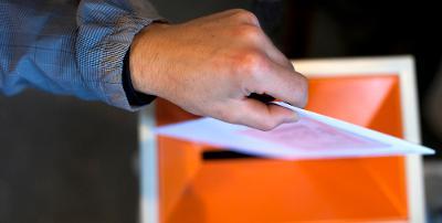Hånd legger stemmeseddel i valgurne. Foto.