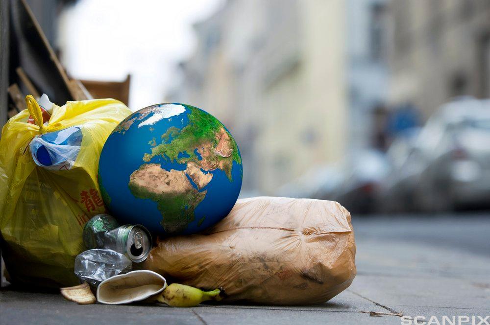 Konseptuelt bilde som illustrerer forbrukersamfunnet: En globus kastet ut på gaten sammen med annet avfall.