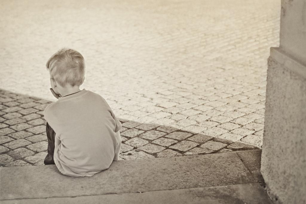 Gutt sitter på steintrapp med ryggen mot kamera.foto.