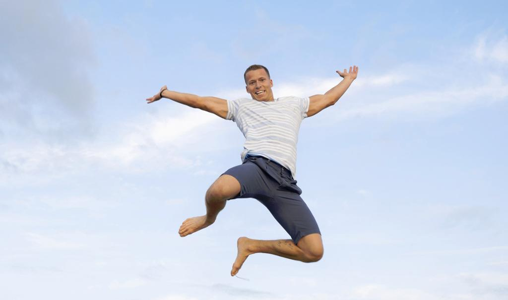 En lykkelig mann gjør et kjempehopp. Foto.