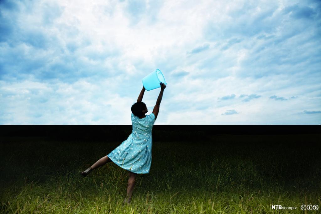 En kvinne i en blå kjole med en bøtte opp mot himmelen med hvite skyer. Foto.