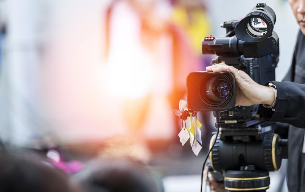 Et stort filmkamera står montert på et stativ. En hånd justerer på objektivet. Foto.