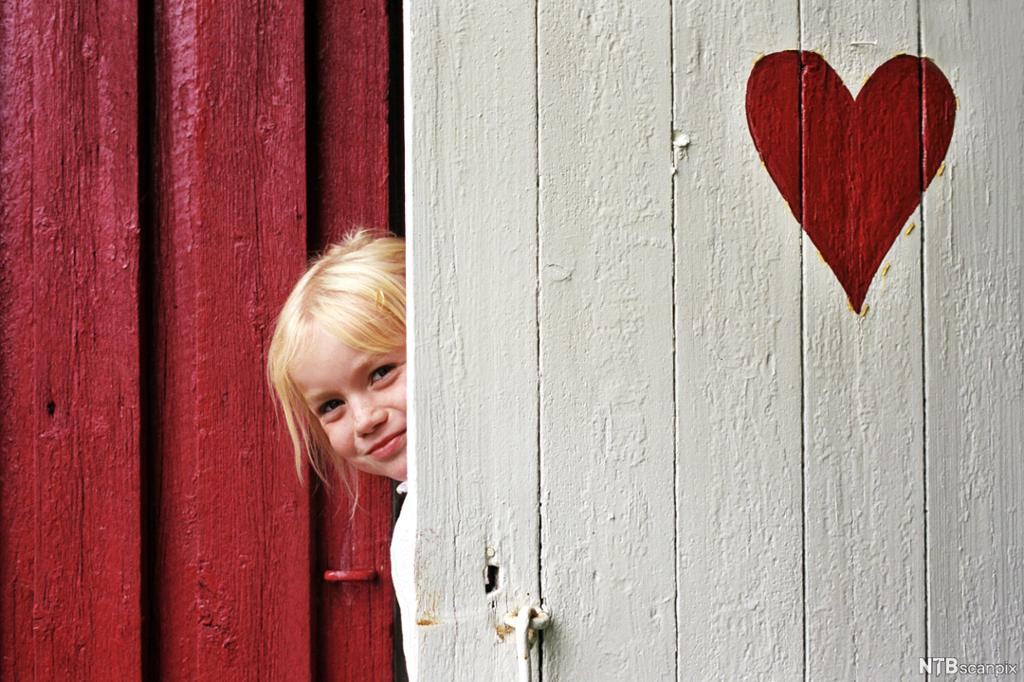 En rød vegg med en lys grå dør med hjerte på, en jente titter ut. Foto.