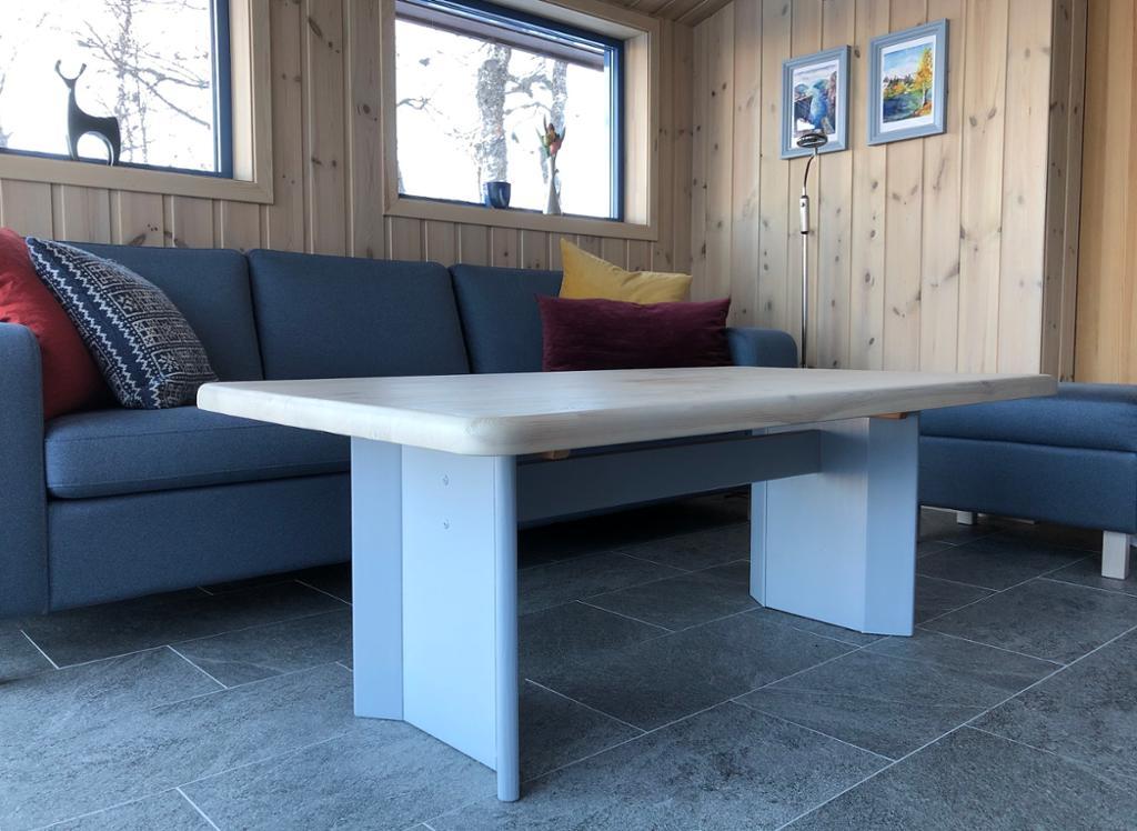 Hytteinteriør: sofa og bord. Foto.