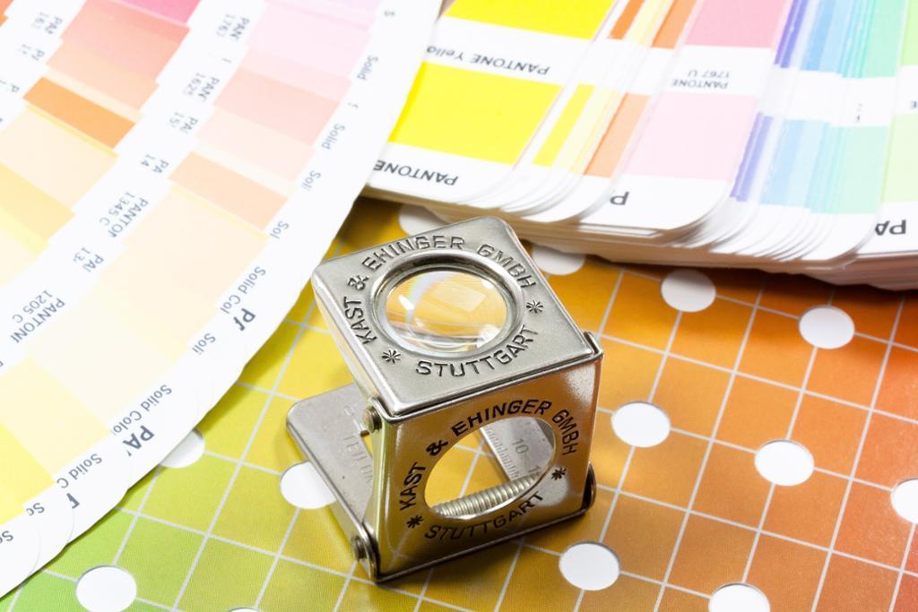Grafisk forstørrelsesglass med Pantone fargekart- Foto.