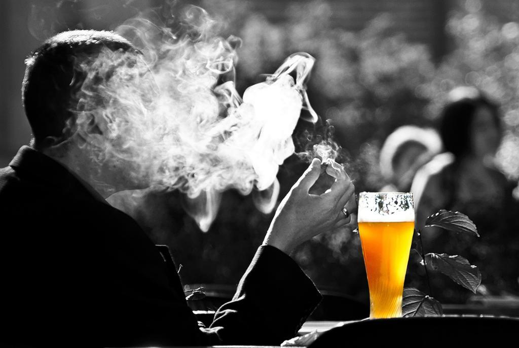 Mann med røyk og øl. Foto.