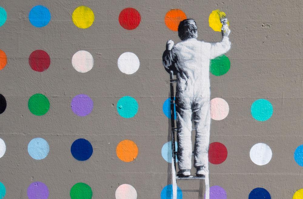 Mann på stige maler fargeprikker. Veggkunst.