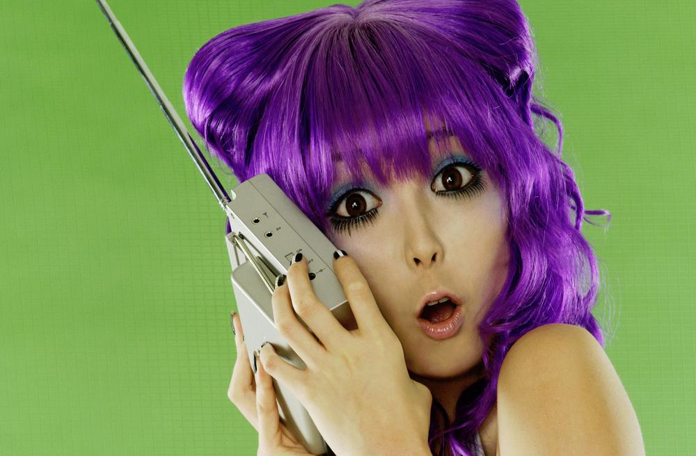 Jente med lilla hår som hører på radio. Foto.
