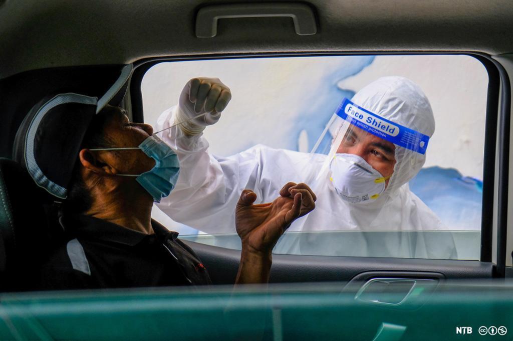 En maskert helsearbeider stikker en bomullspinne opp i nesen på en mann som sitter i en bil. Foto.