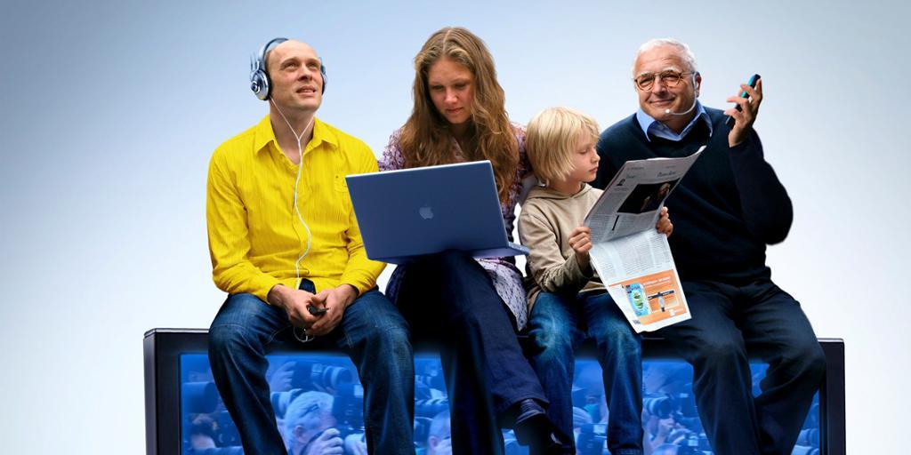 Fire personer i ulike aldre sitter på et TV-apparat med avis, lydavspiller, PC og mobil. Foto.