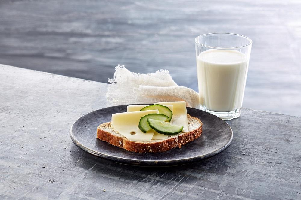 Et glass melk og en brødskive med ost. Foto.