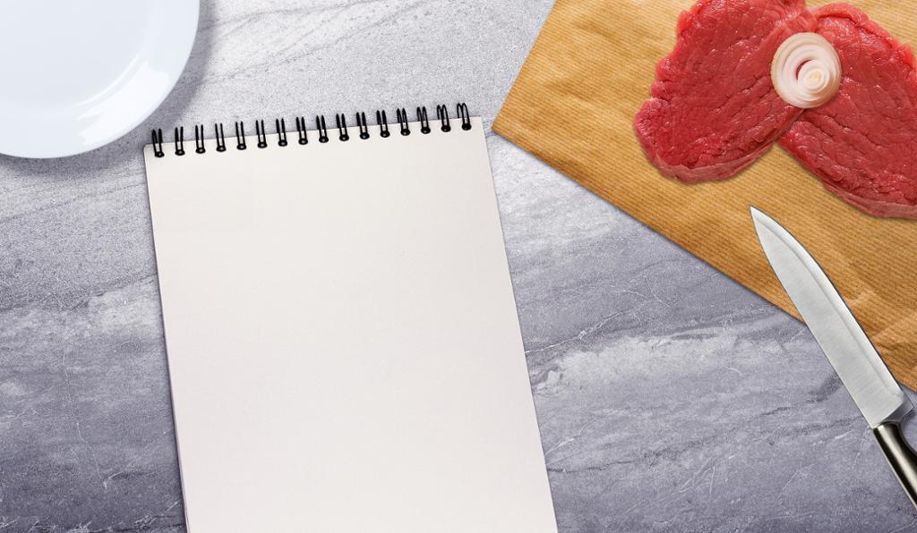 To biffer  på fjør, kokkekniv og notatblokk på et bord.foto.