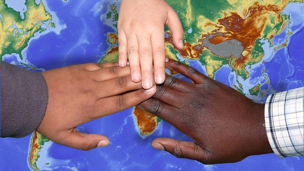 Hender med ulik hudfarge ligger over hverandre på et verdenskart. foto.