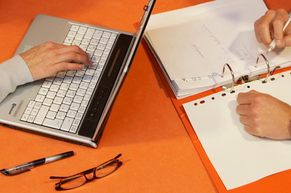 Nærbilde av hendene til noen som noterer på PC og på papir. Foto.