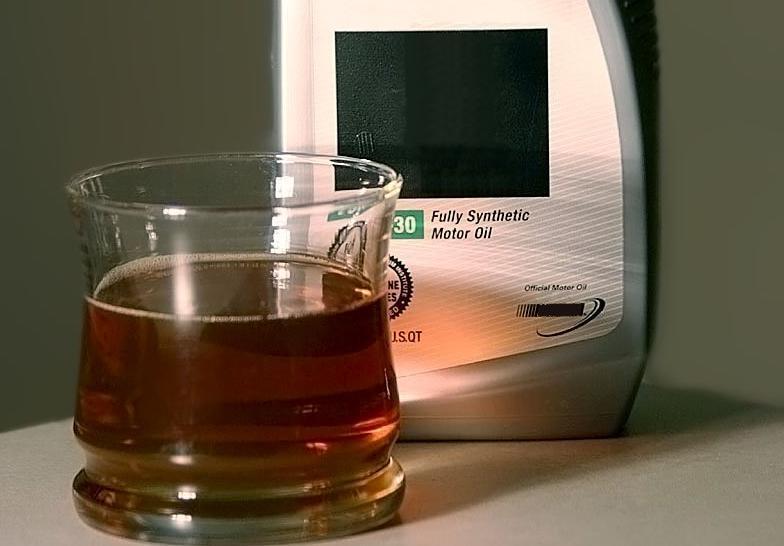 Flaske med motorolje og eit glass med olje framføre. Foto.