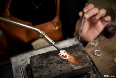 Gullsmed loddar eit metallarbeid. Foto.