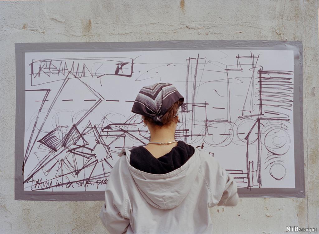 Ei jente med hettegenser og bandana taggar på ein vegg. Foto.