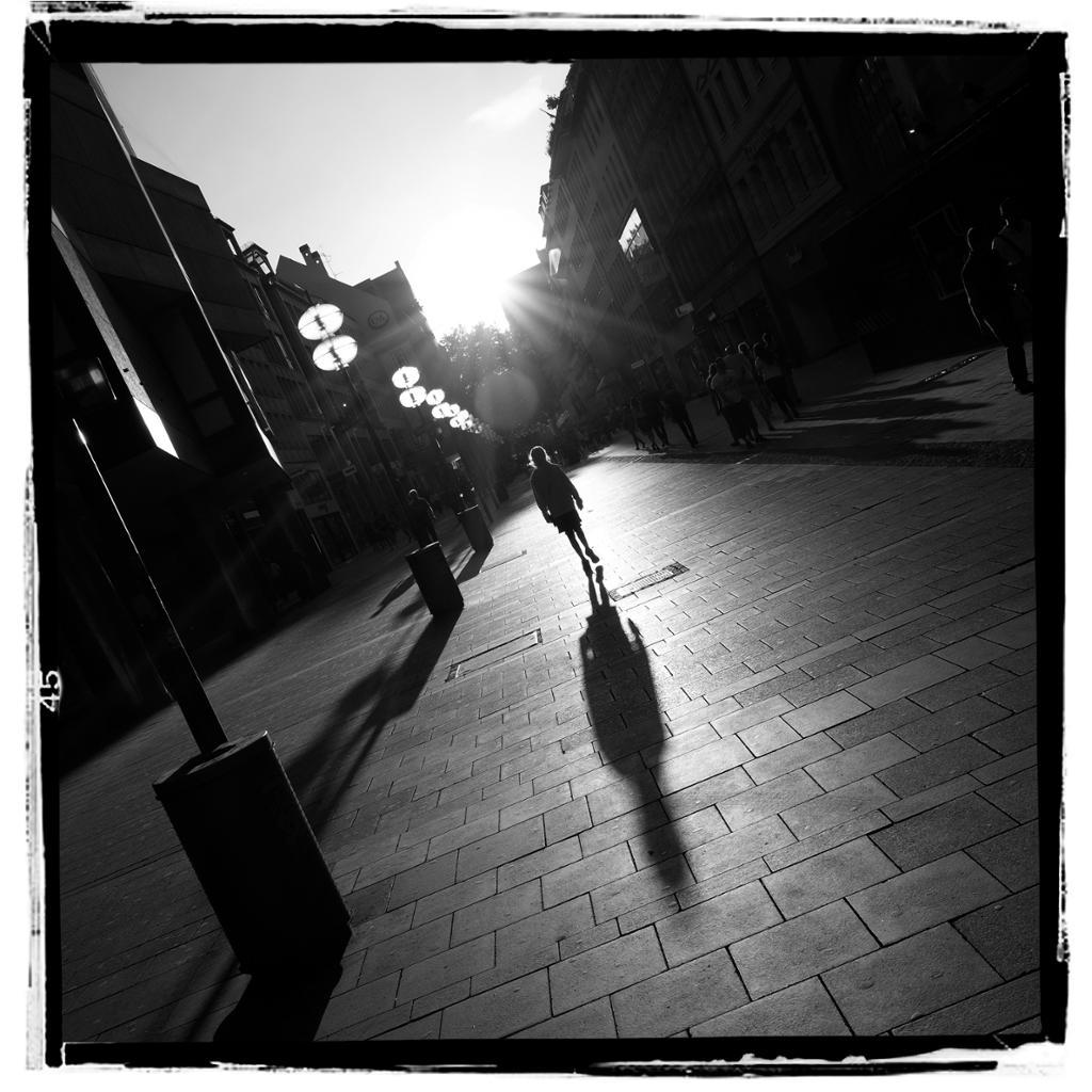Jente vandrer oppover en tom gate i silhuett mot sola. Foto.