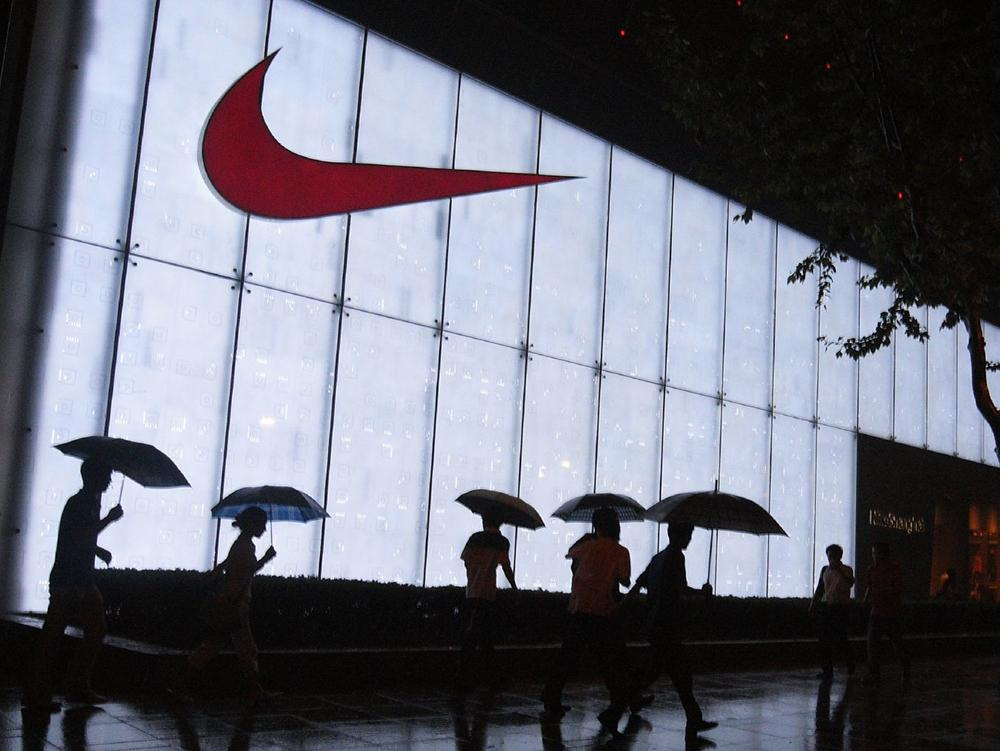 Mennesker med paraply går foran en Nike-bygning nattestid. Foto.