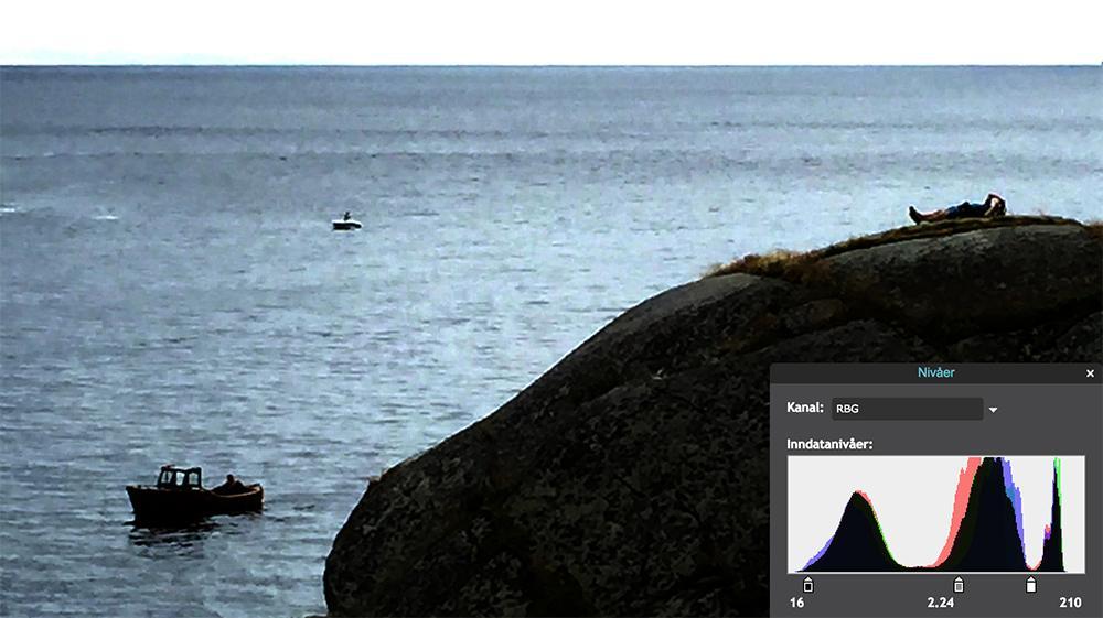 Båt på sjøen og mann som soler seg på svaberg. Foto.