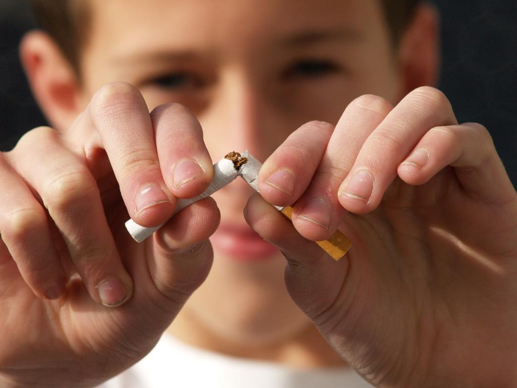 Gutt som knekker en sigarett i to. Foto.