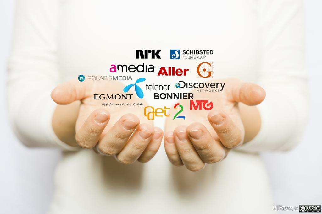 Hånd som holder mange ulike medielogoer. Manipulert fotografi.