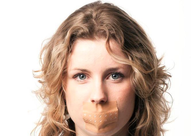 Kvinne med plaster over munnen. Foto.