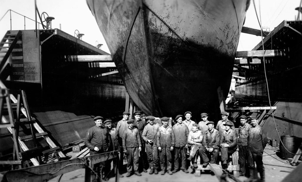 Arbeidere forant et stort skip å hvalfangststasjonen Grytviken, Sør-Georgia. Foto.