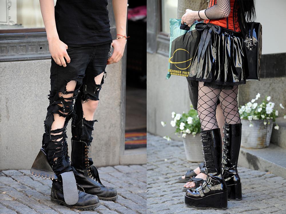 Beina til to ungdommar kledde i sort, holete tøy, naglar,  nettingstrømper og skinnstøvlettar. Foto.