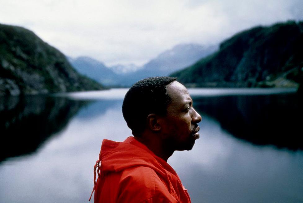 Portrett av mørkhudet mann med norsk fjord i bakgrunnen. Foto.