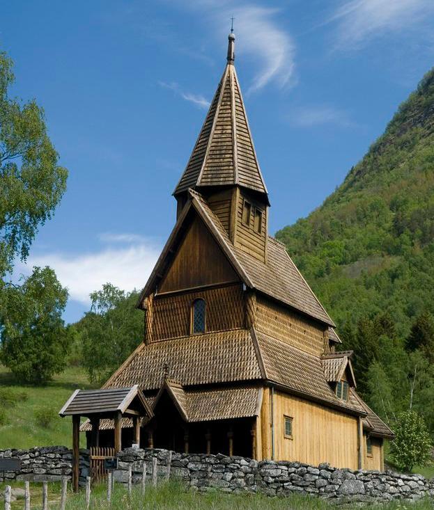 Urnes stavkirke i grønne omgivelser med steinmur foran og fjell bak. Foto.