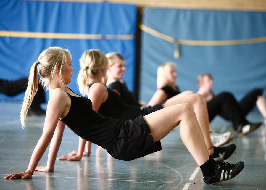Kroppsøvingstime med elever som gjør styrkeøvelser. Foto.