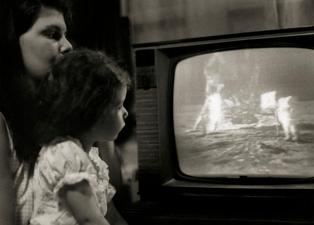 Kvinne med barn på fanget ser astronauter ta de første skritt på månens overflate på fjernsyn. Foto.