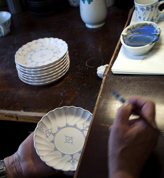 Høyre hånd holder en pensel. Venstre hånd holder en ferdigmalt keramikktallerken med stråmønster. Foto.