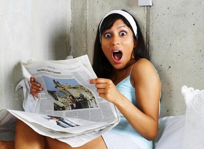 Ung kvinne leser en avis. Foto.