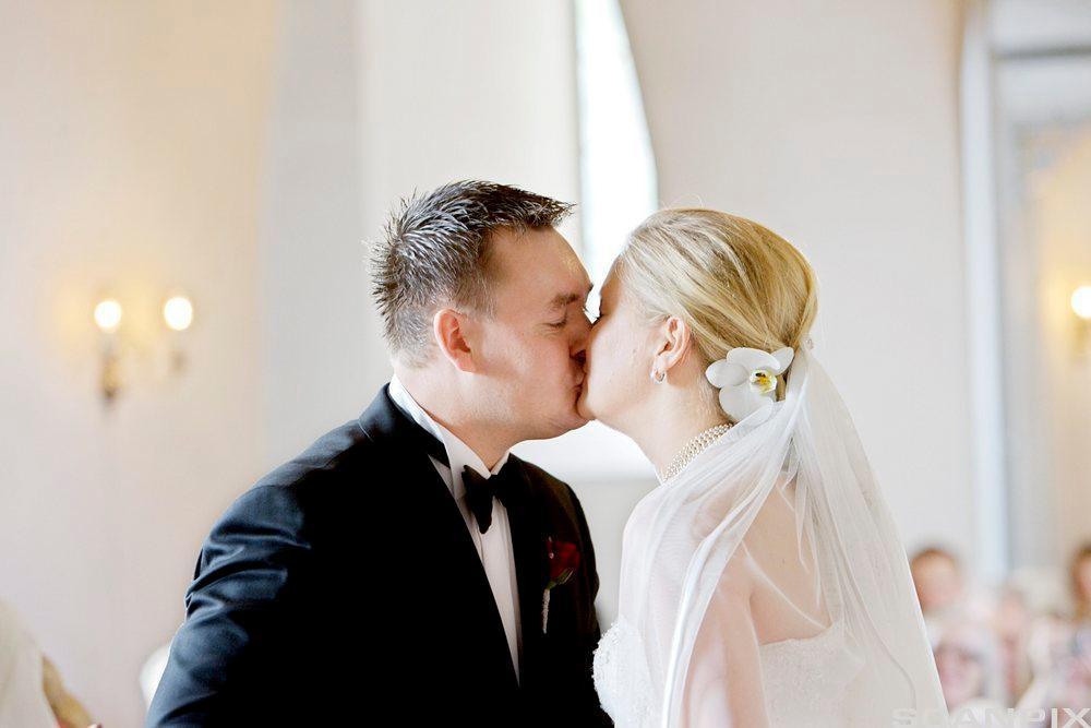 Ein mann og ei kvinne som giftar seg, kyssar kvarandre. Foto.