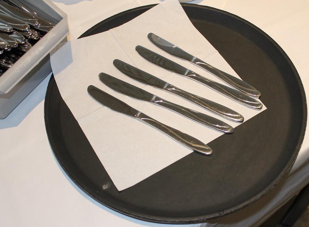 Nypolerte kniver ligger på et fat. Foto.