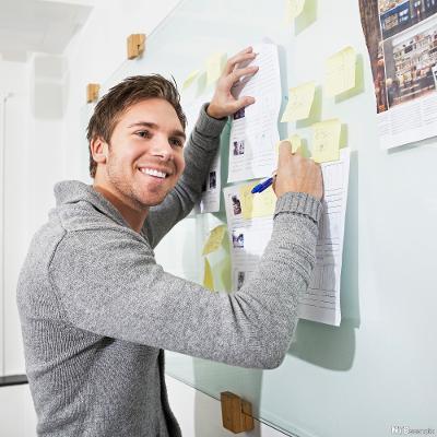 Mann skriver på lapper på veggen. Foto.
