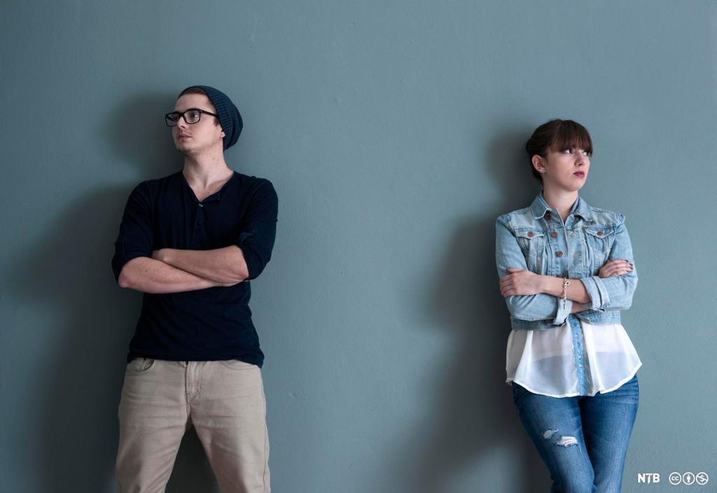 Ein ung mann og ei ung kvinne står ein meter frå kvarandre framfor ein vegg. Begge har armane i kryss og ser vekk frå den andre. Foto.