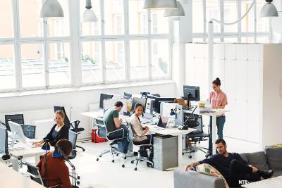 En rekke medarbeidere i et moderne kontorlandskap, sett ovenfra. Foto.