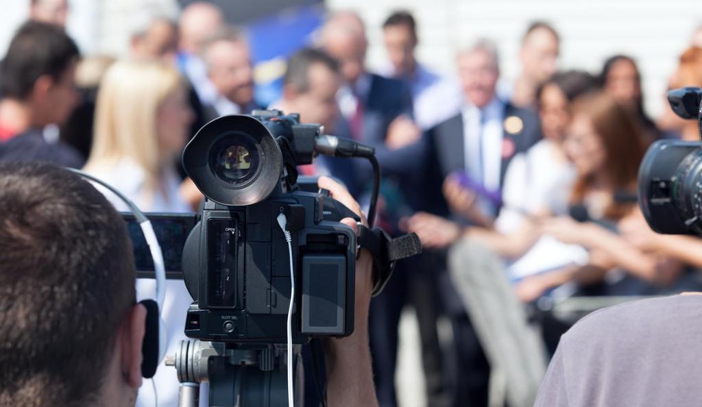 Journalister og fotografer på jobb, en fotograf gjør opptak av intervju. Foto.