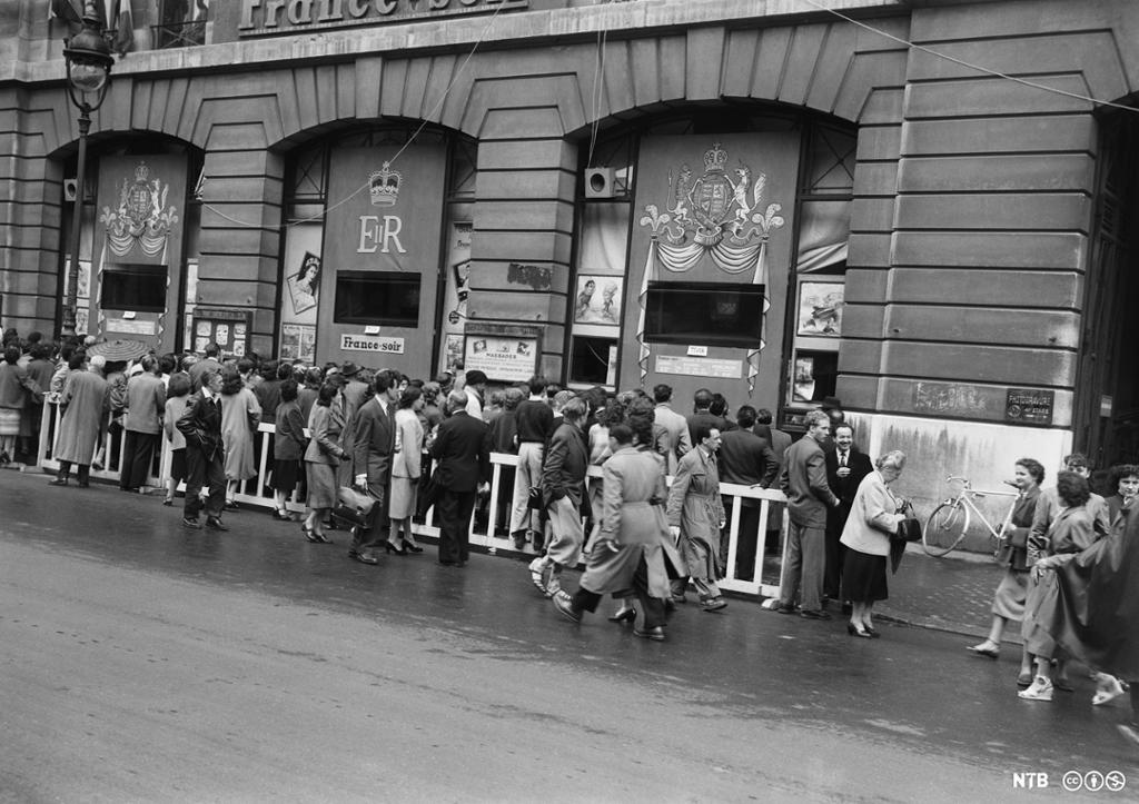 En stor folkemengde stimler sammen foran butikkvinduer. Foto.