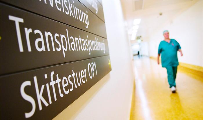 En grønnkledd kirurg går i en sykehusgang. Foto.