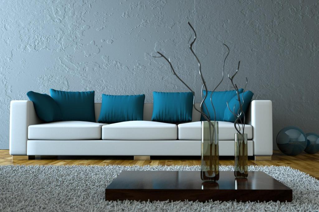Bordplate med vasar og ein kvit sofa med blå puter i eit gråblått rom. Foto.