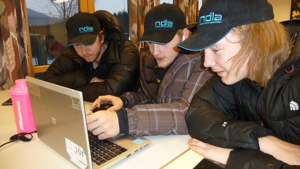 Tre gutter med NDLA-caps arbeider sammen med PC. Foto.