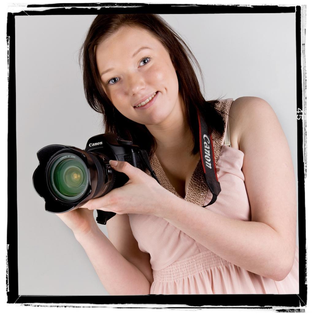 Jente i rosa kjole holder et speilreflekskamera. Foto