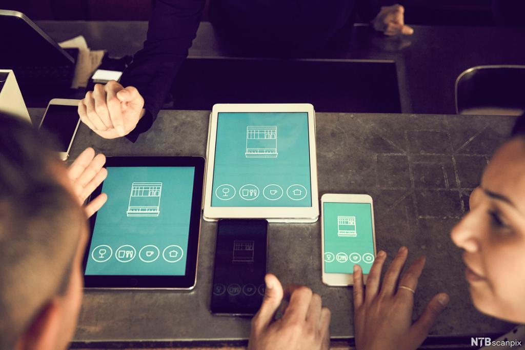 Mann og kvinne med ulike skjermer med app. Foto.