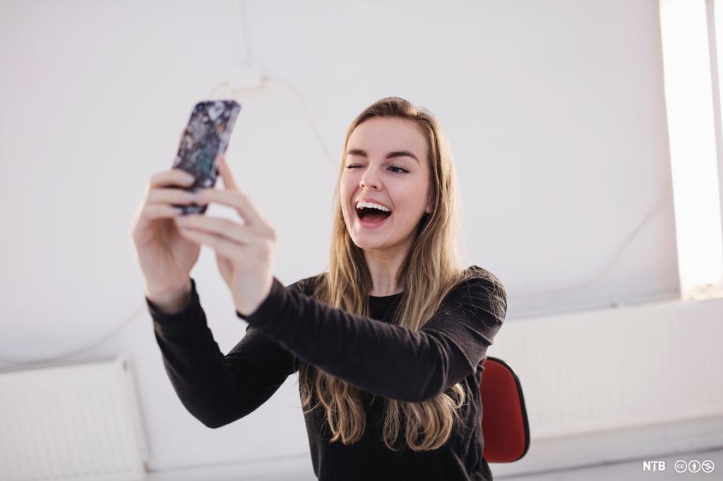 En kvinne smiler og blunker med øye mens hun tar en selfie. Foto.