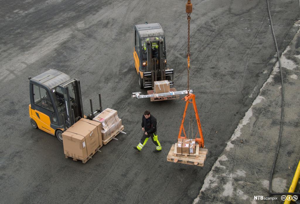To gaffeltrucker og en mann på kai der varer heises . foto.